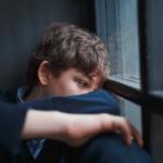 Boy looking sad on his own, poor mental wellbeing